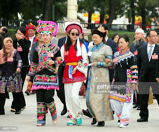 Chinese citizens in different ethnic clothes walk toward to the People's Heroes Monument during the commemoration ceremony for first Martyrs' Day in...