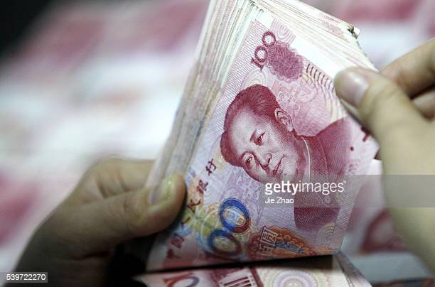 Chinese clerk counts RMB yuan banknotes at a bank in Huaibei , Anhui province, China 1 December 2015.The International Monetary Fund agreed Monday to...