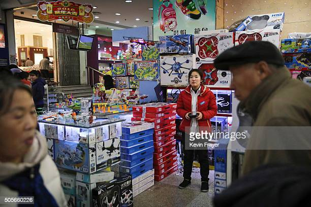 Chinese clerk demonstrates a toy drone at a market on January 19 2016 in Beijing China In 2015 China's economy grew at its slowest rate in a quarter...