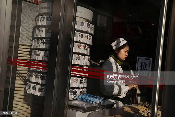 Chinese clerk waits for customers at a department store on January 19 2016 in Beijing China In 2015 China's economy grew at its slowest rate in a...