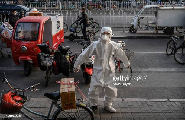 Chinese clerk wears a protective mask and suit as he stretches outside a store on February 28 2020 in Beijing China The number of cases of the deadly...