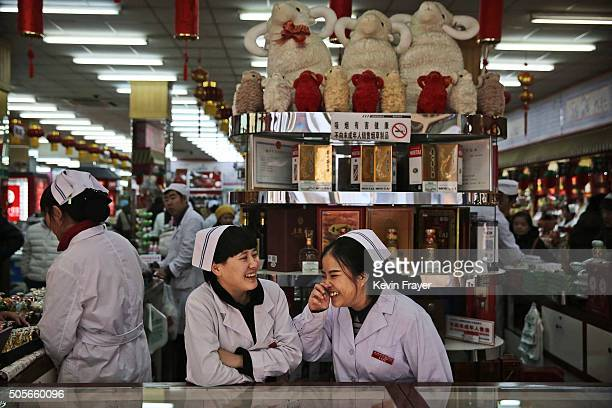 Chinese clerks chat as they wait for customers at a market on January 19 2016 in Beijing China In 2015 China's economy grew at its slowest rate in a...