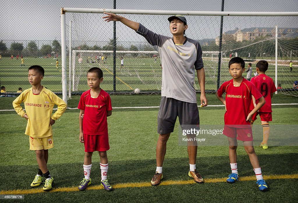 A Chinese coach shouts to players as young students wait to be subbed in during a training match at the Evergrande International Football School on June 14, 2014 near Qingyuan in Guangdong Province, China. The sprawling 167-acre campus is the brainchild of property tycoon Xu Jiayin, whose ambition is to train a generation of young athletes to establish China as a football powerhouse. The school is considered the largest football academy in the world with 2400 students, more than 50 pitches and a squad of Spanish coaches through a partnership with Real Madrid.