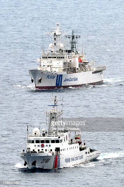 Chinese Coast Guard vessel cruises with Japan Coast Guard patrol ship at the contiguous zone near disputed Senkaku Island on the day Japan marks the...