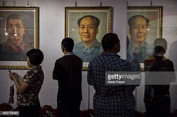 Chinese collectors look at a portrait of the late Mao Zedong next to Karl Marx at a sale and auction of memorabilia dedicated to him on September 19...