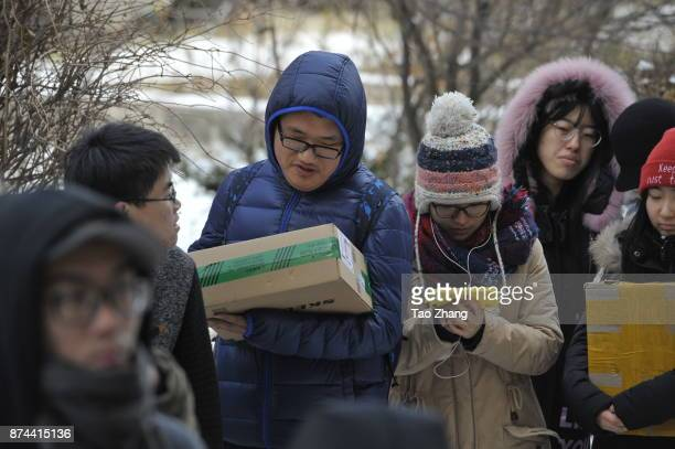 Chinese college students wait to get Singles Day shopping parcels as the outdoor temperature reaches minus 15 at a temporary tent in Heilongjiang...