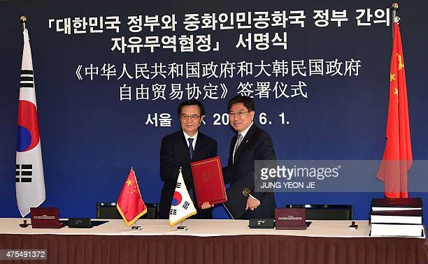 Chinese Commerce Minister Gao Hucheng and South Korean Trade Minister Yoon SangJick pose for a photo during a signing ceremony for a bilateral free...