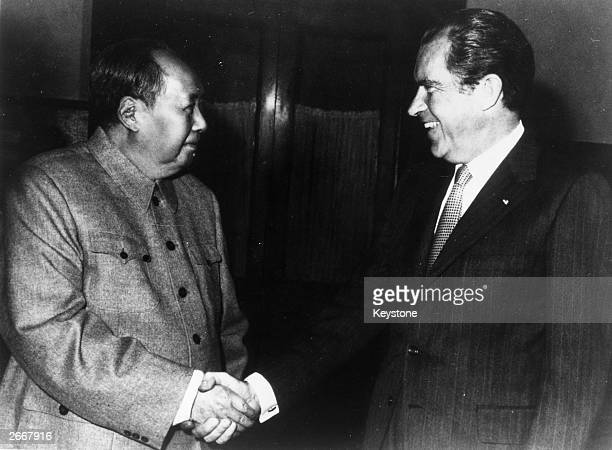 Chinese communist leader Chairman Mao Zedong shakes hands with American president Richard Nixon in Peking during his visit to China.