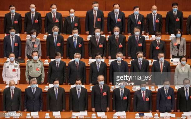 Chinese Communist Party delegates, all wearing protective masks, stand during the national anthem at the opening of the National People's Congress at...