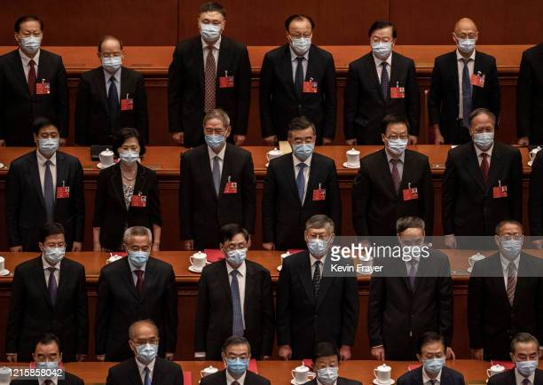 Chinese Communist Party delegates wear protective masks as they stand for the national anthem during the closing session of the National People's...
