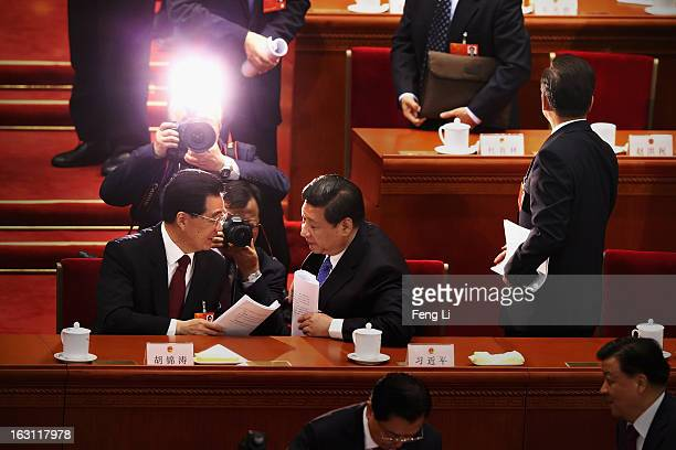 Chinese Communist Party General Secretary Xi Jinping talks with Chinese President Hu Jintao after Chinese Premier Wen Jiabao delivered his work...