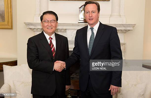 Chinese Communist Party official Li Changchun shakes hands with British Prime Minister David Cameron during their meeting at Downing Street in...