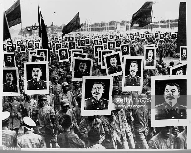 Chinese Communists carry posters with pictures of Joseph Stalin Communist leader They are celebrating the first anniversary of the Communist regime...