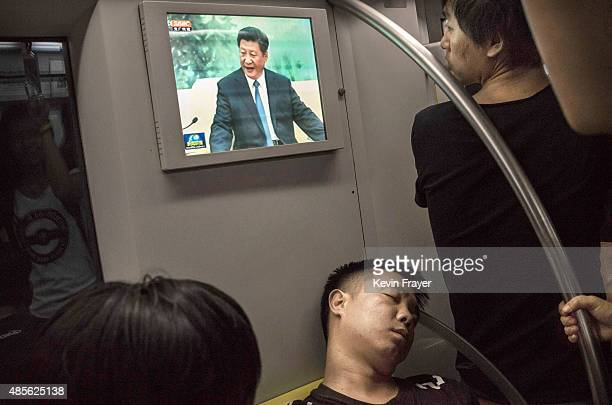 Chinese commuter sleeps as a television shows China's president Xi Jinping on the metro during rush hour on August 28 2015 in Beijing China China's...