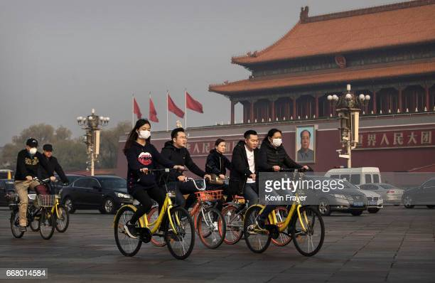 Chinese commuters ride bike share through Tiananmen Square on March 29 2017 in Beijing China The popularity of bike shares has exploded in the past...