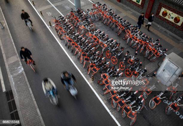 Chinese commuters ride past a large group of Mobike ride share bicycles at a distribution area during rush hour on April 11 2017 in Beijing China The...