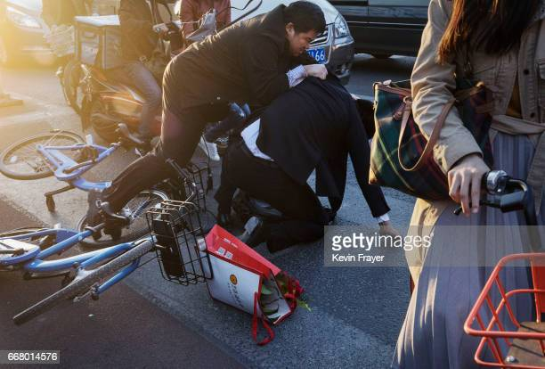Chinese commuters scuffle on the ground after colliding on ride share bicycles during rush hour on April 11 2017 in Beijing China The popularity of...