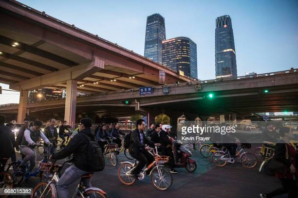 Chinese commuters some on ride share bicycles cross an intersection during rush hour on April 11 2017 in Beijing China The popularity of bike shares...