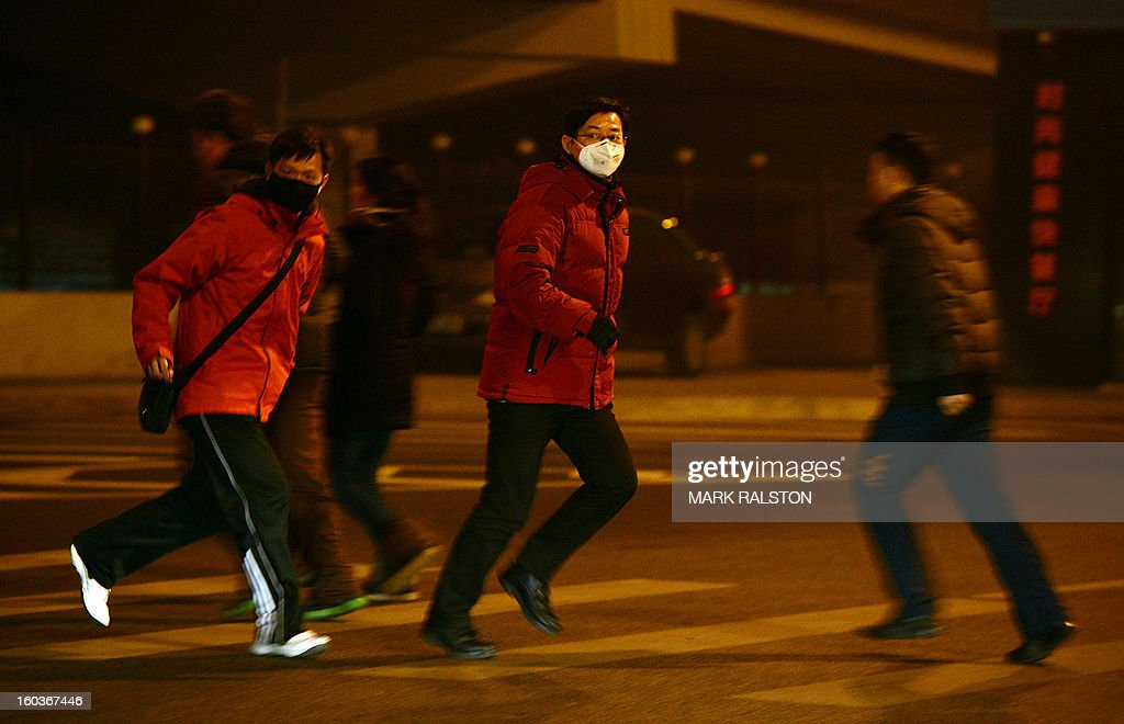 Chinese commuters wear face masks as they cross a central business district road during heavy air pollution in Beijing on January 30, 2013. Beijing urged residents to stay indoors as emergency measures were rolled out aimed at countering a heavy cloud of smog blanketing the Chinese capital and swathes of the country. The municipal government said children, the elderly and people sensitive to poor air quality should remain indoors, after authorities announced the closure of 103 factories and ordered 30 percent of official cars off the road. AFP PHOTO/Mark RALSTON