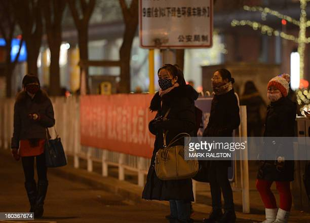 Chinese commuters wear face masks as they cross a central business district road during heavy air pollution in Beijing on January 30 2013 Beijing...