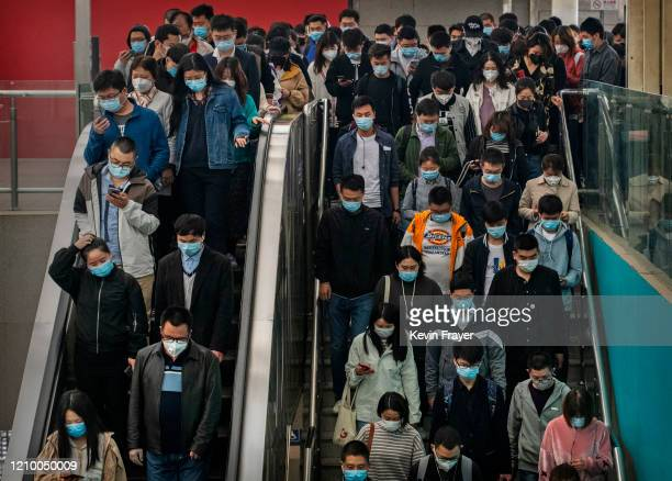 Chinese commuters wear protective masks as they crowd on an escalator and stairs after getting off the subway during rush hour on April 15, 2020 in...