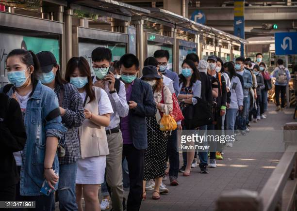Chinese commuters wear protective masks as they line up in a crowd to catch a bus at the end of the workday during rush hour on May 18, 2020 in...