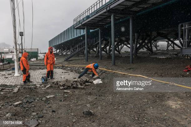 Chinese company CEIEC employees paving the flag square in front of Comandante Ferraz Station during a blizzard on December 23 2019 in King George...