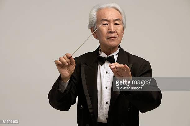chinese conductor holding baton - maestro stock photos and pictures