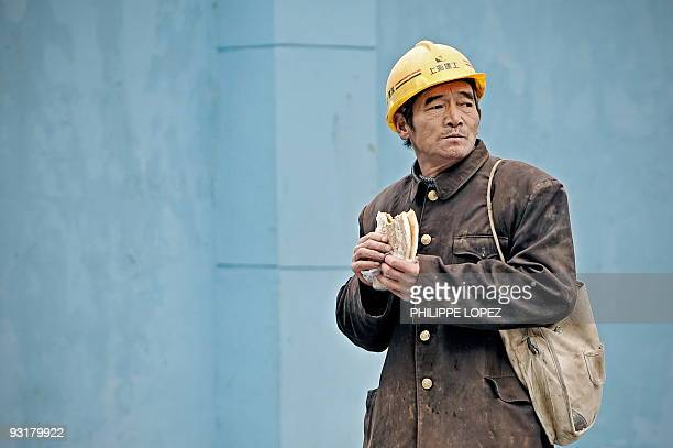 A Chinese construction worker eats a piece of bread as he walks along a building site during a break in Shanghai on November 18 2009 As US President...