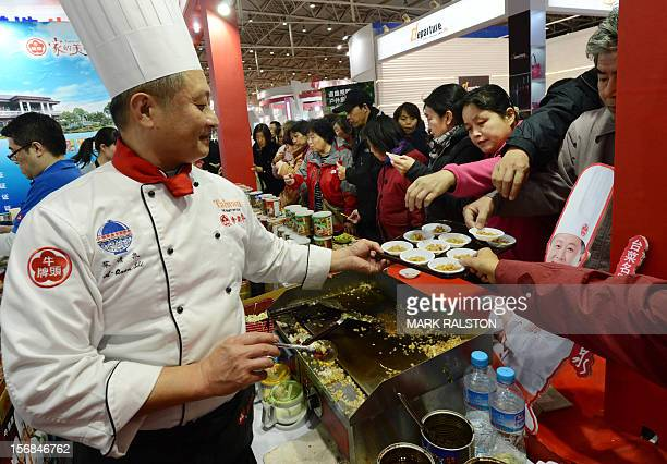Chinese consumers sample food from Taiwan during a Taiwanese food fair as the demanded for imported food becomes more common in Beijing on November...