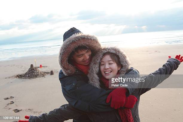 chinese coule on beach in winter - newpremiumuk stock pictures, royalty-free photos & images
