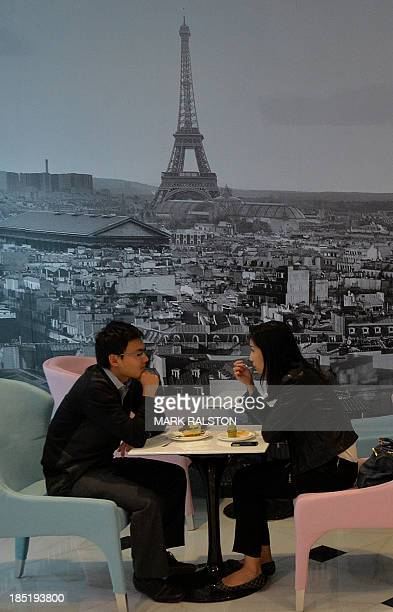 A Chinese couple eat French desserts beneath a picture of the Eiffel Tower in the Galeries Lafayette department store during its official opening in...