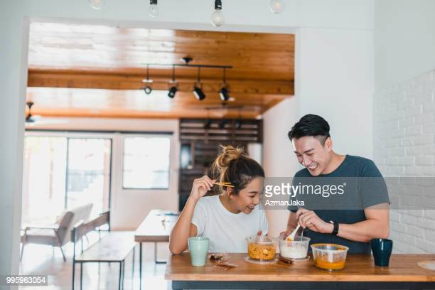 chinese couple eating noodles in domestic kitchen - domestic life imagens e fotografias de stock