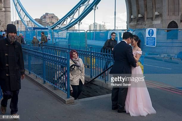 A Chinese couple have their wedding photos taken amid the chaotic repairs to London's Tower Bridge on 6th October 2016 in London England Closed for...