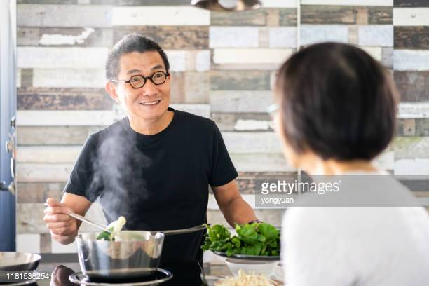 chinese couple in the kitchen - heterosexual couple stock pictures, royalty-free photos & images