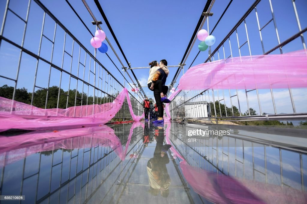 Chinese couple kiss as they stand on a glass bridge during a kissing contest on Valentine's Day in Pingjiang, central China's Hunan province on February 14, 2017. / AFP PHOTO / STR / China OUT