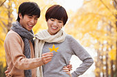 chinese couple looking at autumn leaf