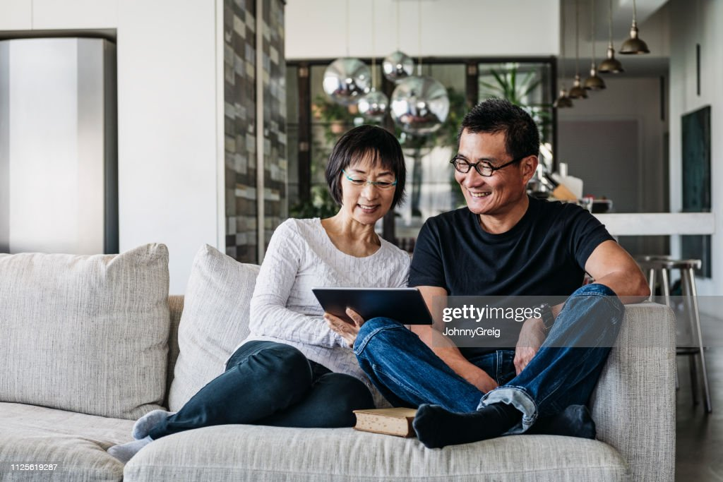 Chinese couple on sofa watching movie online : Stock Photo