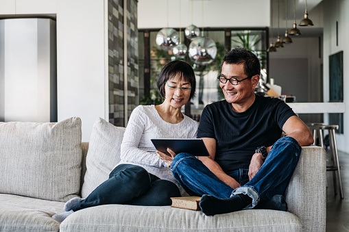 Chinese couple on sofa watching movie online 1125619287