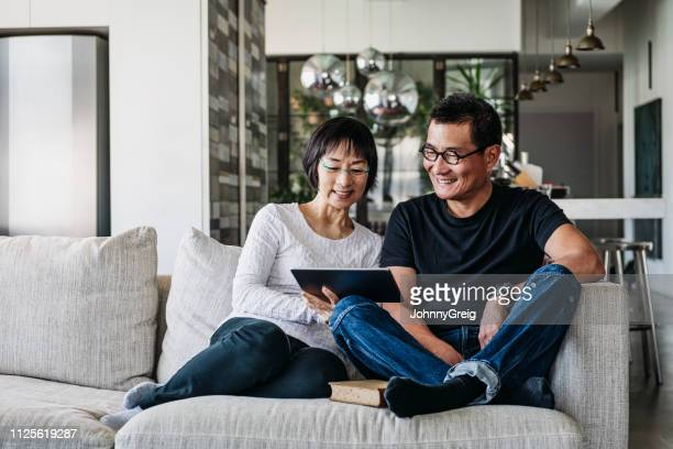 chinese couple on sofa watching movie online - mood stream stock pictures, royalty-free photos & images