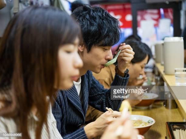 東京バカンス中国カップル日本ラーメン屋 - man eating woman out ストックフォトと画像