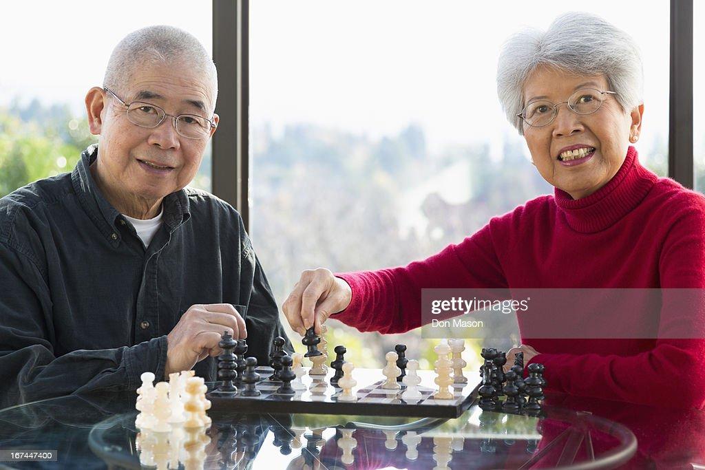 Chinese couple playing chess : Stock Photo