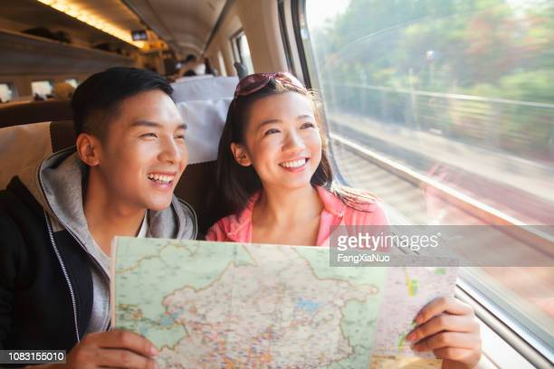 chinese couple reading map on train - asia map stock pictures, royalty-free photos & images