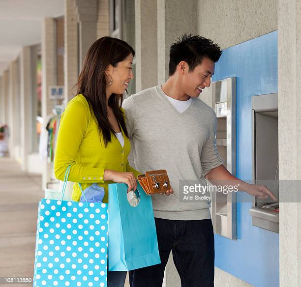 Chinese couple removing money from ATM