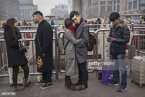 Chinese couple share a moment as they say goodbye to each other before traveling home at Beijing Railway Station on January 26 2017 in Beijing China...