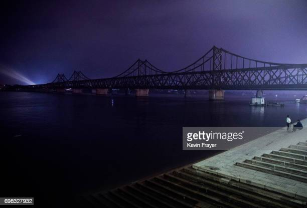A Chinese couple sit next to the 'Friendship Bridge' on the Yalu river in the border city of Dandong Liaoning province northern China across from the...