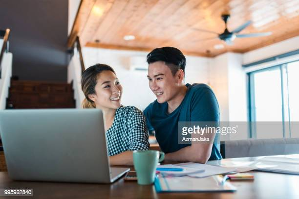 chinese couple using a laptop in the living room and planning a vacation - asia foto e immagini stock