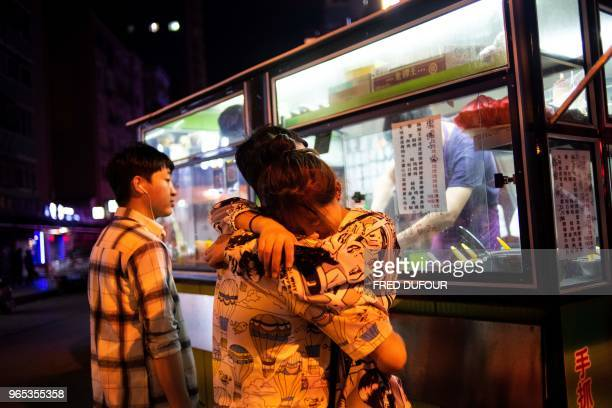 A Chinese couple waits for their order from a street vendor in the Chinese border town of Dandong in China's northeast Liaoning province on May 30...