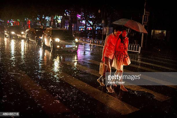 Chinese couple walk together under an umbrella on a rainy evening on September 4 2014 in Beijing China
