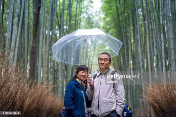 chinese couple walking in arashiyama bamboo grove - arashiyama stock pictures, royalty-free photos & images